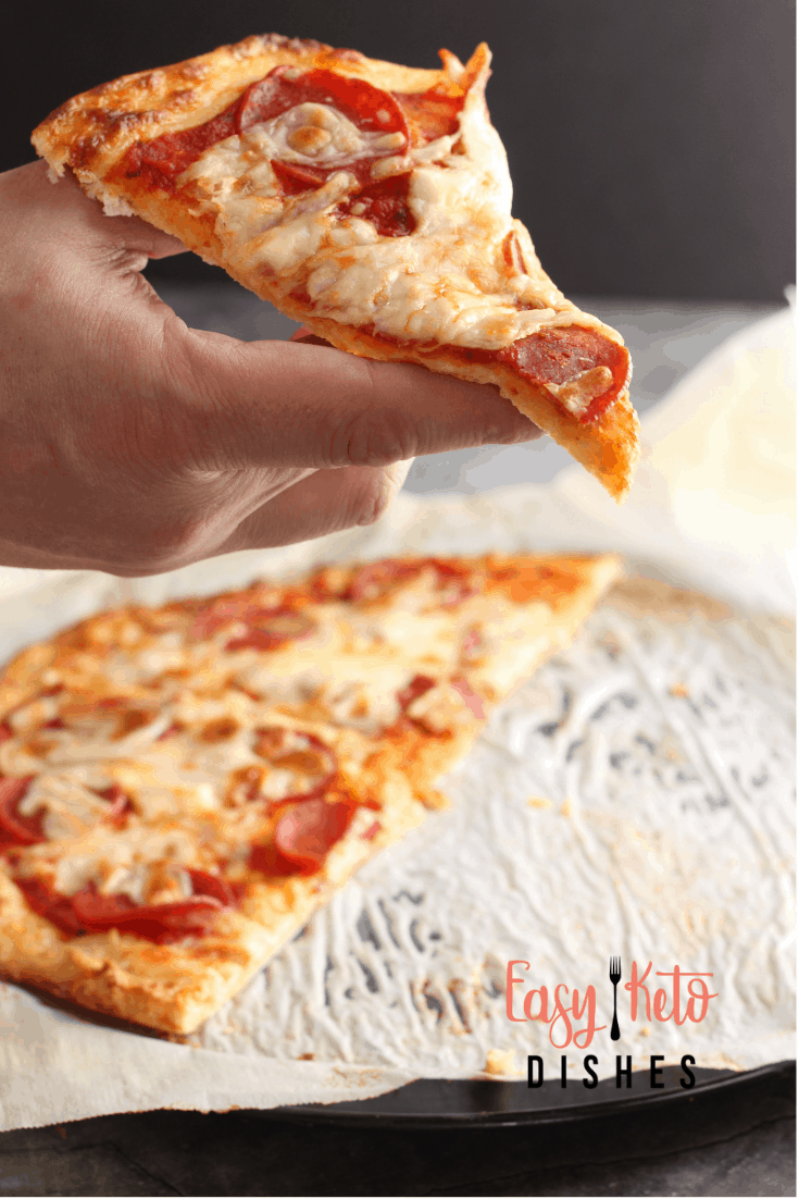 holding single slice of keto crust pizza