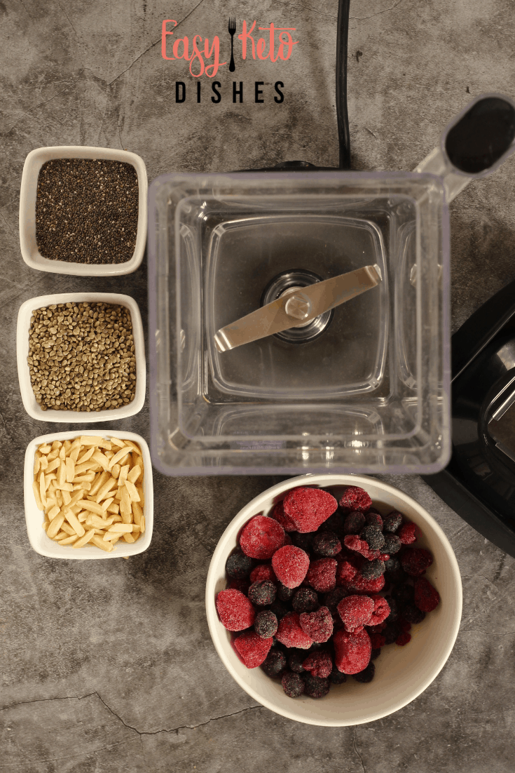 open blender with frozen fruit, chia seeds, hemp hearts, and almonds