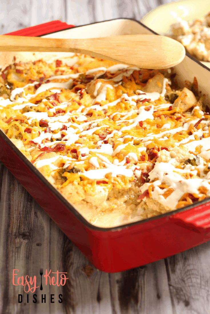 chicken bacon ranch casserole in red casserole dish with wooden spoon