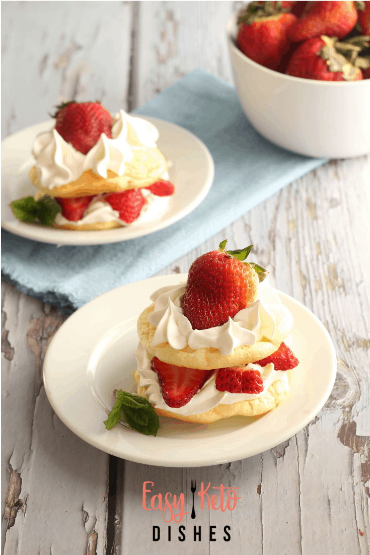 strawberry shortcakes on white plate with bowl of strawberries