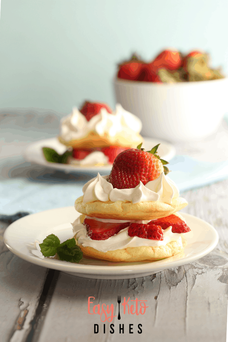 keto strawberry shortcakes on white plates with bowl of strawberies in back