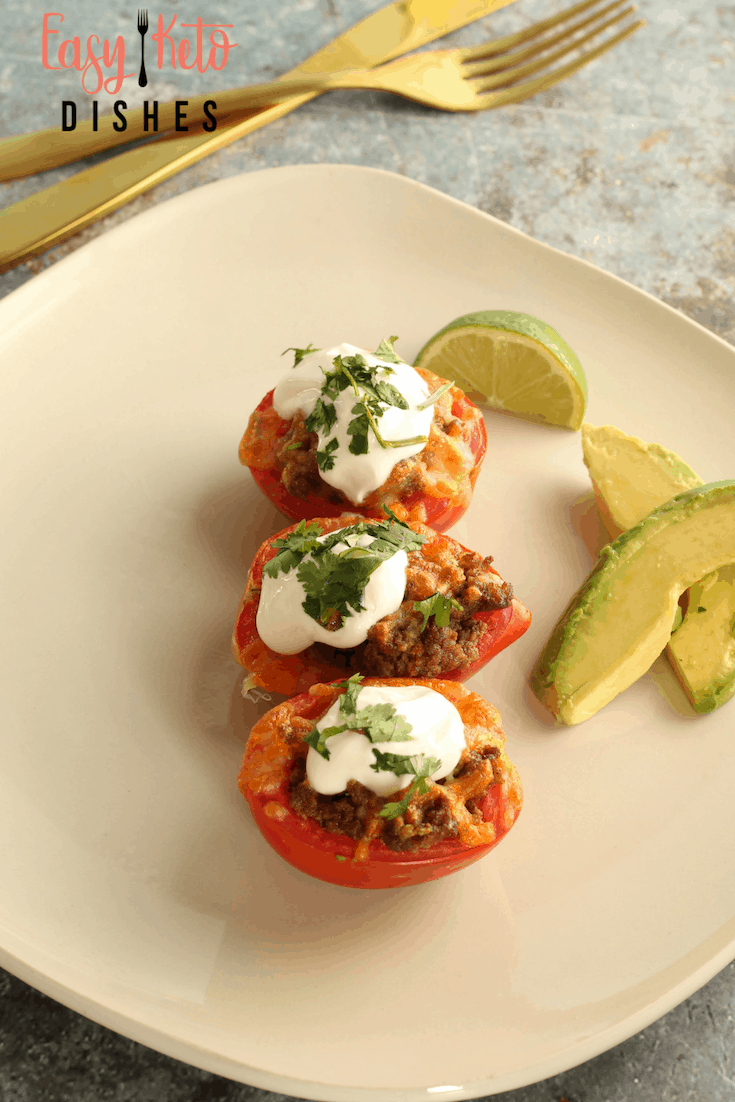 taco stuffed tomatoes on white plate with avocado slices and lime wedge