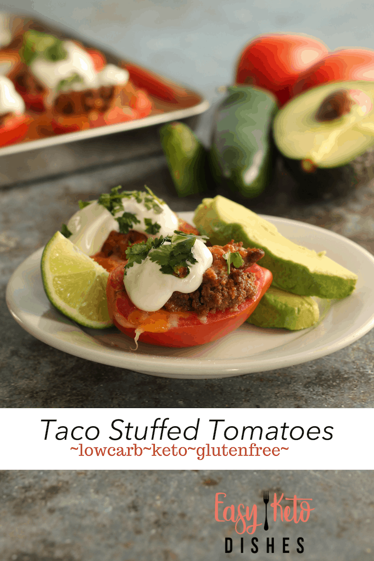 taco stuffed tomatoes on plate with avocado slices and lime wedge