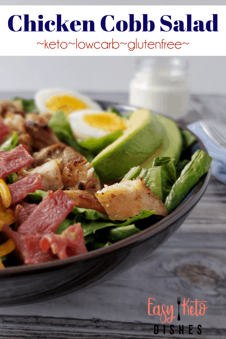side view of keto cobb salad, showing chicken, bacon bits, and avocado slices