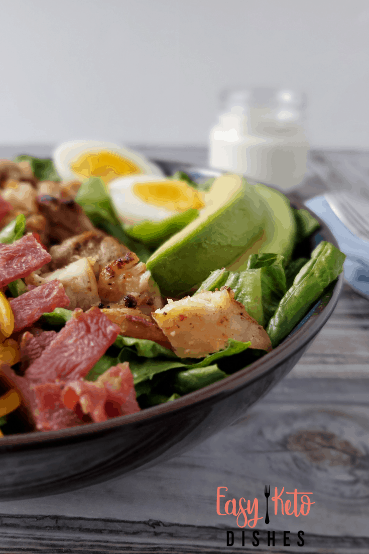 side view of salad, showing bacon and egg, and chicken pieces