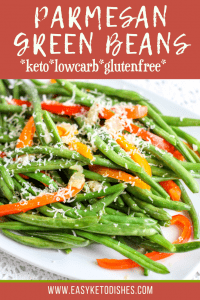 green beans and red peppers with parmesan on white plate